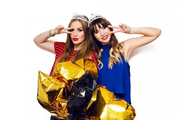 Porträt von zwei hübschen frauen mit hellen partyballons