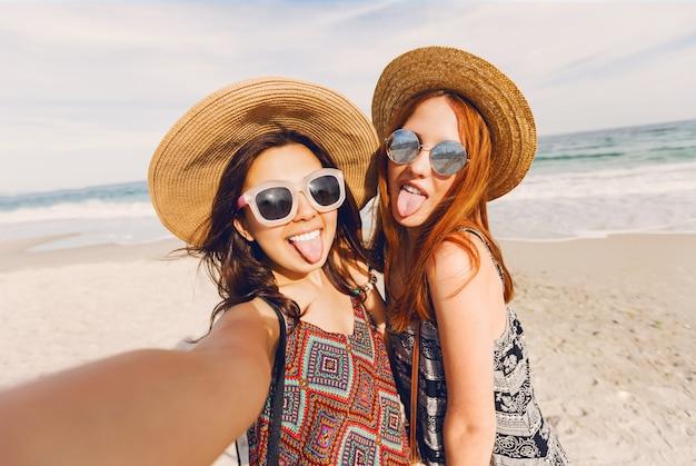 Porträt von zwei hübschen frischen jungen besten freundinnen, die selbstporträt machen und spaß am strand haben