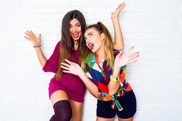 Porträt von zwei hübschen jugendlich freundinnen, die lächeln und posieren