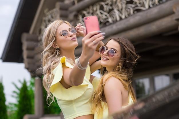 Porträt von zwei hübschen jungen brautjungfern in gelben kleidern nahe einem modischen holzhaus. menschen lifestyle-konzept. selfie schuss auf handy lächelnd und luftkuss senden