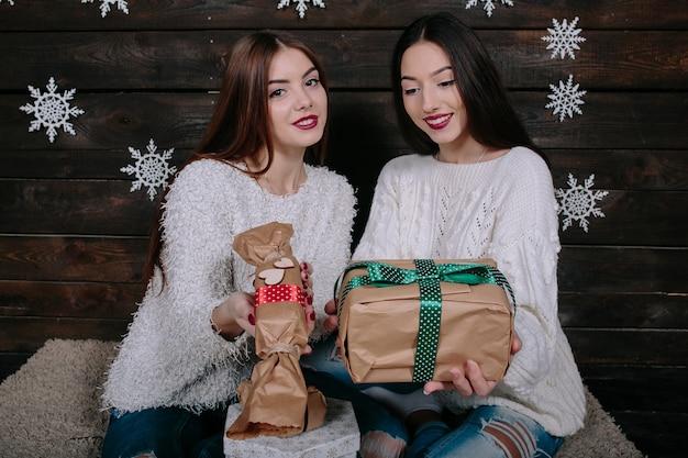 Porträt von zwei hübschen jungen frauen mit weihnachtsgeschenken