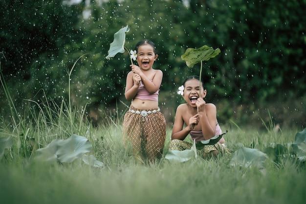 Porträt von zwei hübschen mädchen in thailändischem trachtenkleid und schöne blume auf ihr ohr setzen, das lotusblatt abnehmen schützen sie die regentropfen mit fröhlichem kopierraum