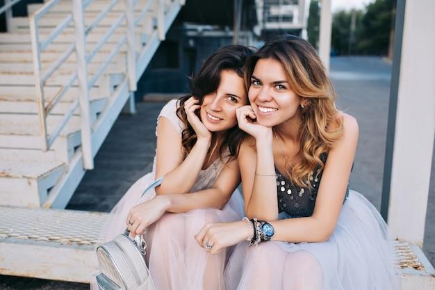 Porträt von zwei hübschen mädchen in tüllröcken, die draußen auf treppen sitzen. sie lächeln.