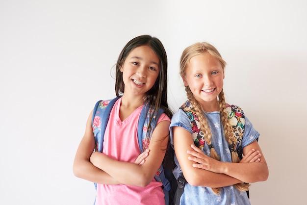 Porträt von zwei hübschen mädchen mit rucksäcken