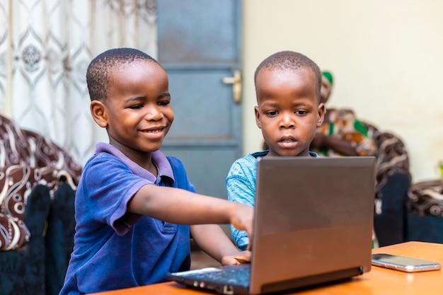 Porträt von zwei jungen afrikanischen kindern zu hause, die spiele online mit laptop spielen. faszienausdruck