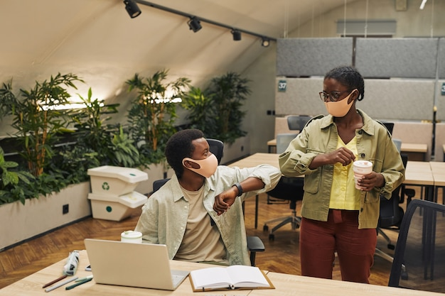 Porträt von zwei jungen afroamerikanern, die ellbogen als kontaktlose begrüßung stoßen, während sie im büro nach der pandemie arbeiten, kopieren raum