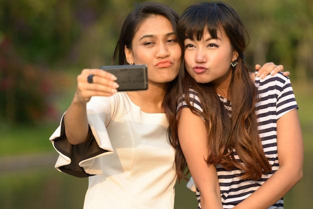Porträt von zwei jungen asiatischen frauen, die zusammen im park draußen entspannen