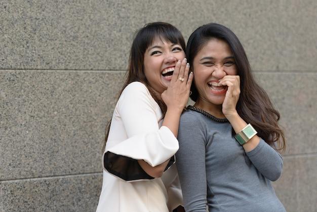 Porträt von zwei jungen asiatischen geschäftsfrauen zusammen in der stadt im freien