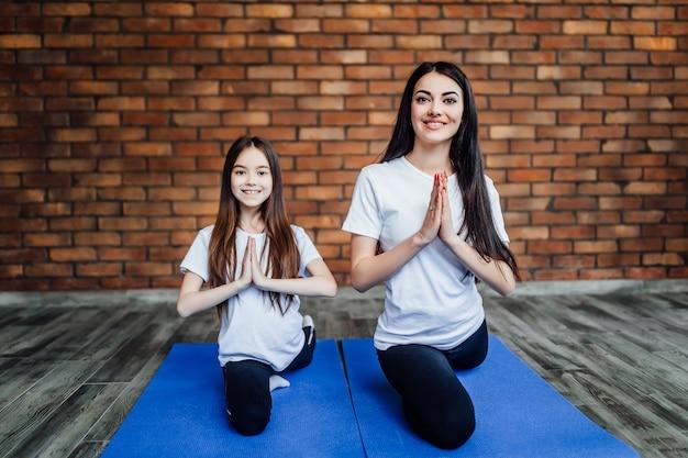 Porträt von zwei jungen flexiblen mädchen, die auf yogamatte sitzen und vor der ausbildung sich vorbereiten. in der yogamitte.
