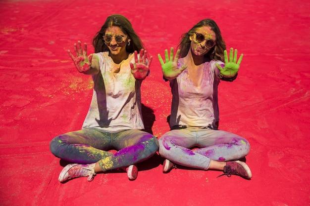 Porträt von zwei jungen frauen, die ihre palmen gemalt mit holi farbe zeigen