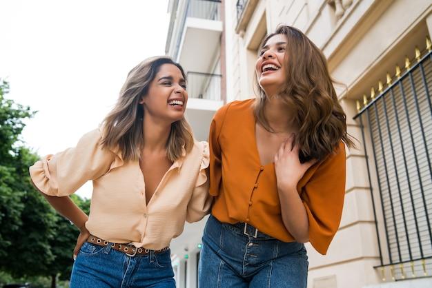 Porträt von zwei jungen freunden, die beim spaziergang im freien gute zeit miteinander verbringen. urbanes konzept.
