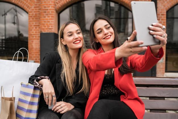 Porträt von zwei jungen freunden, die ein selfie mit digitalem tablett nehmen, während sie draußen mit einkaufstüten sitzen