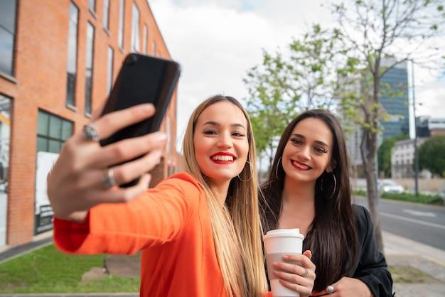 Porträt von zwei jungen freunden, die ein selfie mit handy auf der straße nehmen. lifestyle- und freundschaftskonzepte.
