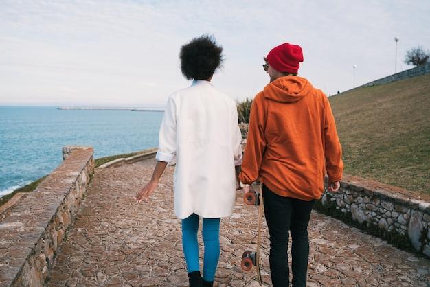 Porträt von zwei jungen freunden, die eine schöne zeit zusammen verbringen, an der küste spazieren gehen und spaß haben.