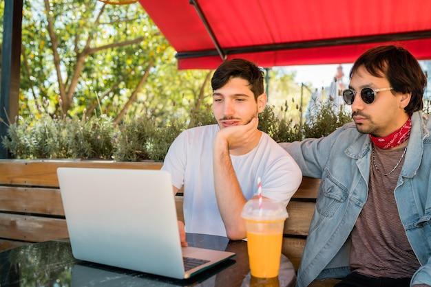 Porträt von zwei jungen freunden, die einen laptop verwenden, während sie draußen im café sitzen. freundschafts- und technologiekonzept.