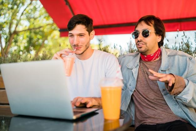 Porträt von zwei jungen freunden, die einen laptop verwenden, während sie draußen im café sitzen