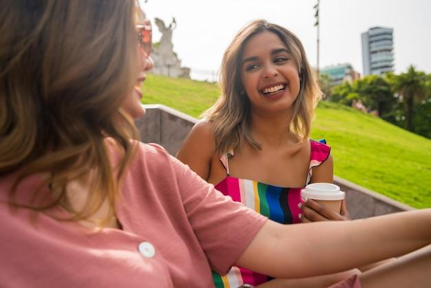 Porträt von zwei jungen freunden, die gute zeit miteinander verbringen und sich unterhalten, während sie im freien auf der treppe sitzen. urbanes konzept.