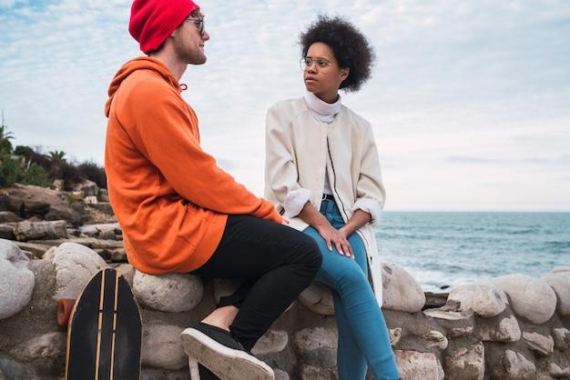 Porträt von zwei jungen freunden, die gute zeit zusammen verbringen und ein gespräch führen, während sie mit dem meer im sitzen.