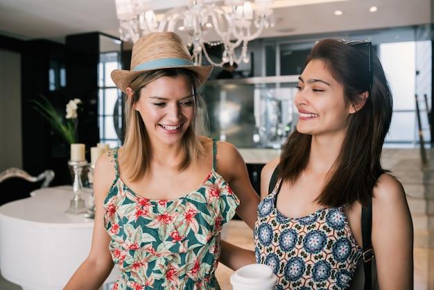 Porträt von zwei jungen freunden, die im hotel ankommen und mit ihrem gepäck durch die lobby gehen. reise- und lifestyle-konzept.