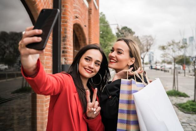 Porträt von zwei jungen freunden, die zusammen einkaufen gehen, während sie ein selfie mit telefon auf der straße machen. freundschafts- und einkaufskonzept.