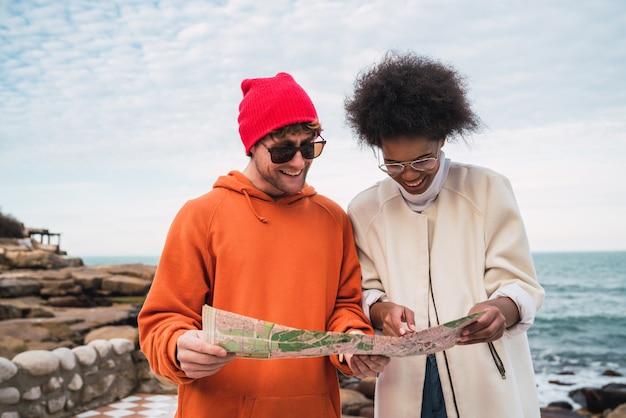 Porträt von zwei jungen freunden, die zusammen reisen, mit einer karte und auf der suche nach dem weg. reisekonzept.