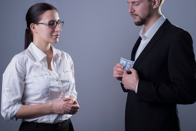 Porträt von zwei jungen geschäftsleuten in geschäftskleidung. eine geschäftsfrau mit brille beobachtet, wie ein mann eine presse mit dollarnoten aus seiner jackentasche holt.