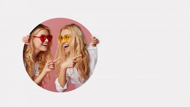 Porträt von zwei jungen glücklichen, schockierten frauen in der herzförmigen sonnenbrille, die durch das weiße loch in der wand schauen. großer verkauf. lustige gesichter. leerraum für text