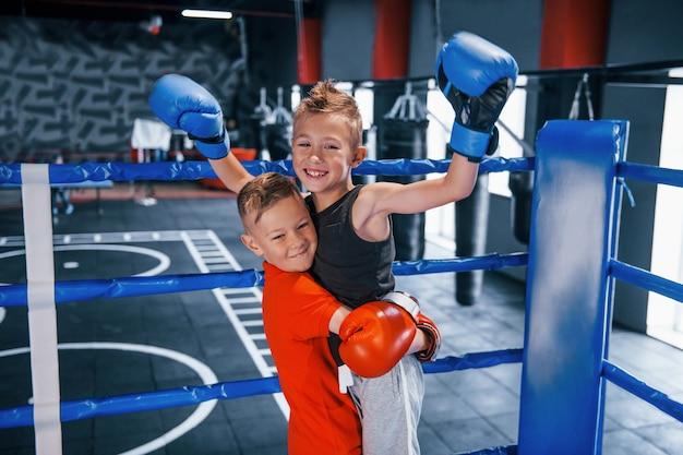 Porträt von zwei jungen in schutzhandschuhen, die den sieg auf dem boxring feiern.