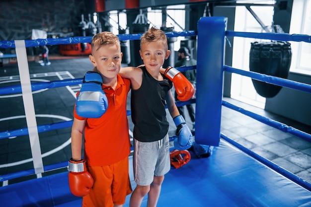 Porträt von zwei jungen in schutzhandschuhen, die zusammen auf einem boxring stehen.