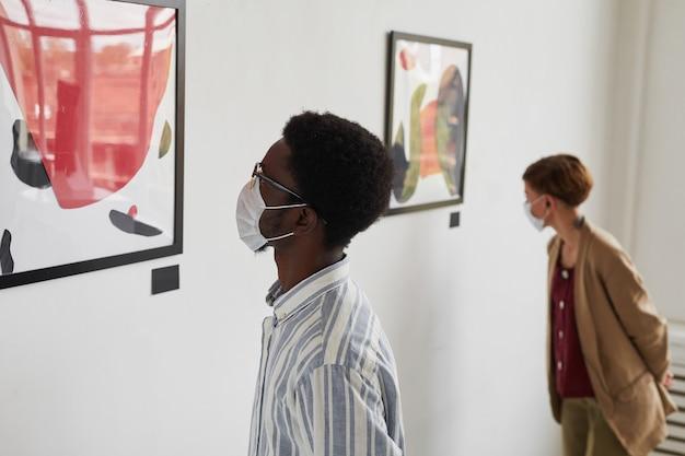 Porträt von zwei jungen leuten, die gemälde betrachten, während sie masken bei der ausstellung der modernen kunstgalerie tragen,