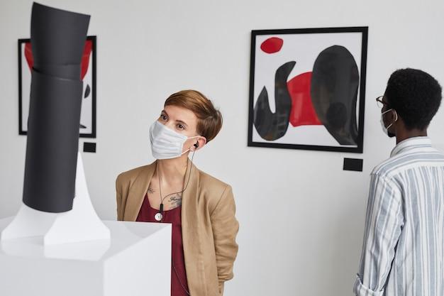 Porträt von zwei jungen leuten, die gemälde und skulpturen betrachten, während sie masken tragen und galerieausstellung der modernen kunst erkunden,