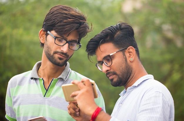 Porträt von zwei jungen männern, die auf handy im freien chatten