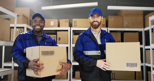 Porträt von zwei jungen männlichen postboten in uniformen und mützen, die kartonschachteln in den händen halten
