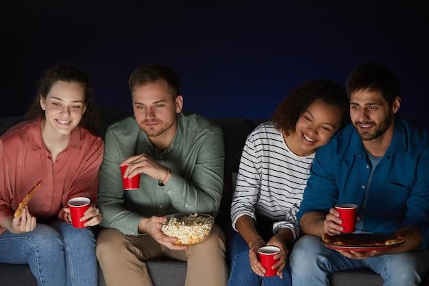 Porträt von zwei jungen paaren, die zu hause filme schauen, während sie snacks und popcorn essen, die auf sofa im dunklen raum sitzen