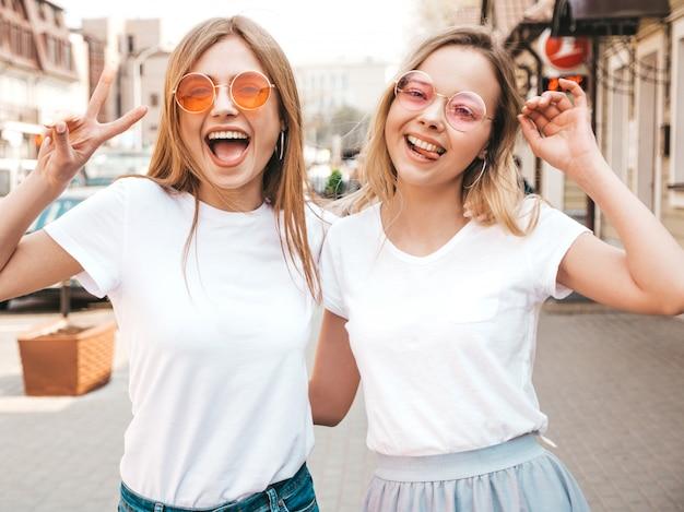 Porträt von zwei jungen schönen blonden lächelnden hippie-mädchen im weißen t-shirt des modischen sommers kleidet. . positive modelle, die spaß haben. zeigt friedenszeichen