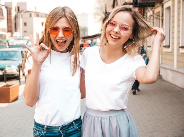 Porträt von zwei jungen schönen blonden lächelnden hippie-mädchen im weißen t-shirt des modischen sommers kleidet. . positive modelle, die spaß in der sonnenbrille haben