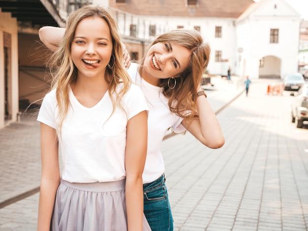 Porträt von zwei jungen schönen blonden lächelnden hippie-mädchen im weißen t-shirt des modischen sommers kleidet. . positive modelle zeigen die zunge