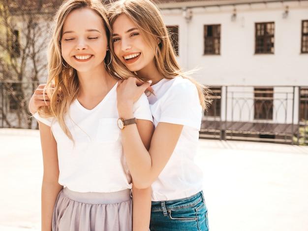 Porträt von zwei jungen schönen blonden lächelnden hippie-mädchen im weißen t-shirt des modischen sommers kleidet. . positive models, die spaß haben