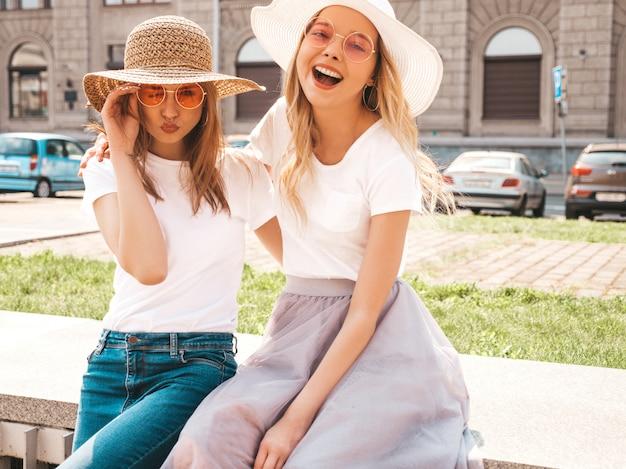 Porträt von zwei jungen schönen blonden lächelnden hippie-mädchen im weißen t-shirt des modischen sommers kleidet.