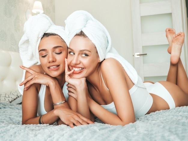 Porträt von zwei jungen schönen lächelnden frauen in weißen bademänteln und handtüchern auf dem kopf