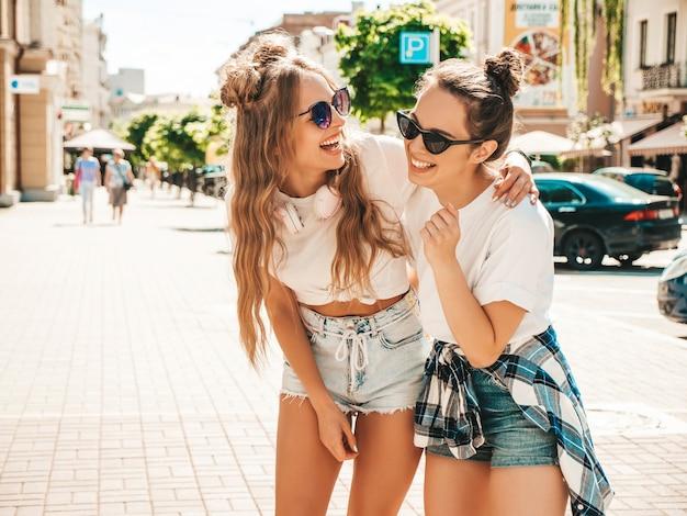 Porträt von zwei jungen schönen lächelnden hippie-frauen in trendiger weißer sommer-t-shirt-kleidung
