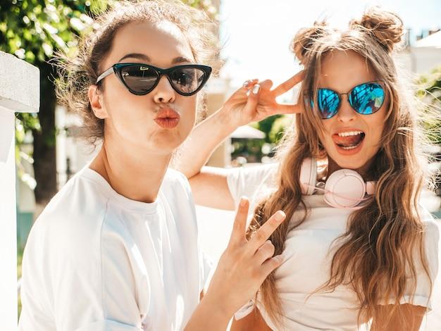 Porträt von zwei jungen schönen lächelnden hippie-mädchen in trendiger weißer sommer-t-shirt-kleidung
