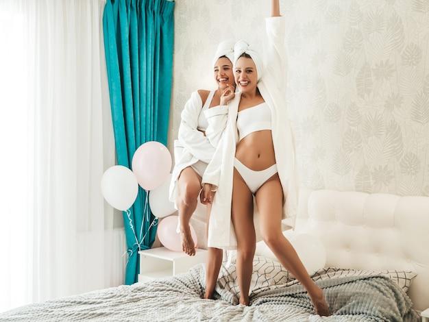 Porträt von zwei jungen schönen lächelnden mädchen in weißen bademänteln und handtüchern auf dem kopf