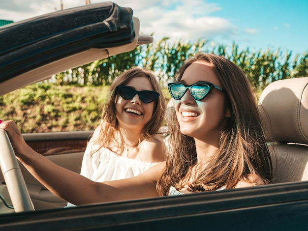 Porträt von zwei jungen schönen und lächelnden hippie-frauen im cabrio
