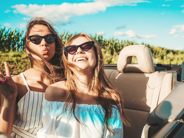 Porträt von zwei jungen schönen und lächelnden hippie-mädchen im cabrio-auto
