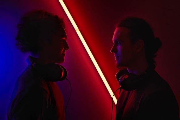 Porträt von zwei jungen spielern in den kopfhörern, die einander betrachten, die gegen den dunklen hintergrund stehen