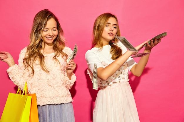 Porträt von zwei jungen stilvollen lächelnden blonden frauen, die einkaufstaschen halten. frauen gekleidet in sommer hipster kleidung. positive modelle, die geld über rosa wand ausgeben