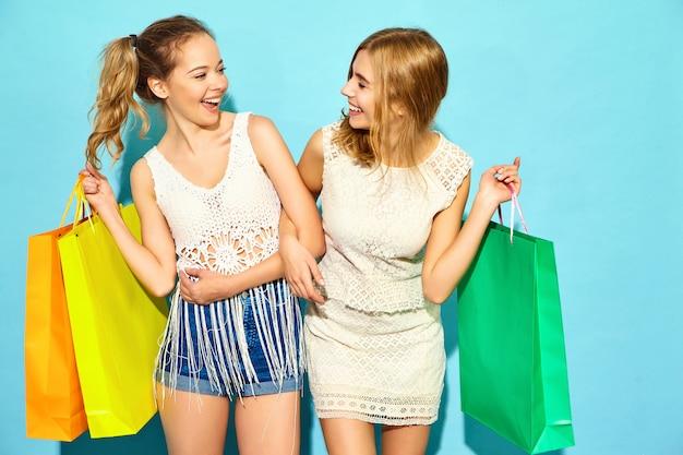 Porträt von zwei jungen stilvollen lächelnden blonden frauen, die einkaufstaschen halten. frauen gekleidet in sommer hipster kleidung. positive modelle, die über blauer wand aufwerfen