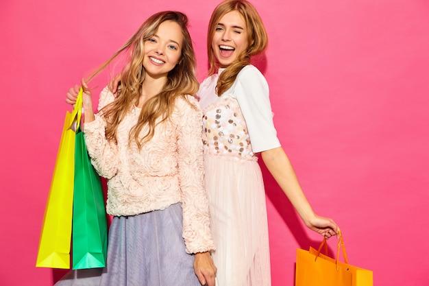 Porträt von zwei jungen stilvollen lächelnden blonden frauen, die einkaufstaschen halten. frauen gekleidet in sommer hipster kleidung. positive modelle, die über rosa wand aufwerfen