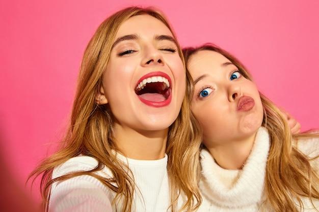 Porträt von zwei jungen stilvollen lächelnden blonden frauen